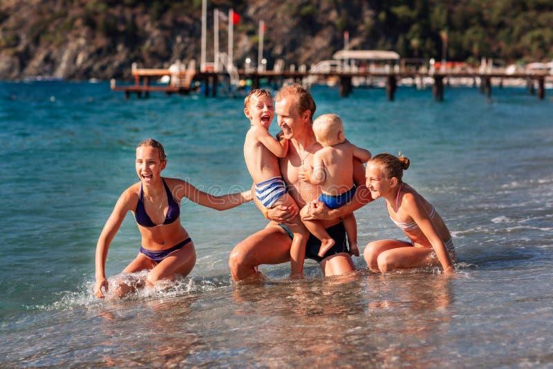 Szczęśliwi dzieciaki z jego ojcem na plażowym mieć zabawę zdjęcie royalty free
