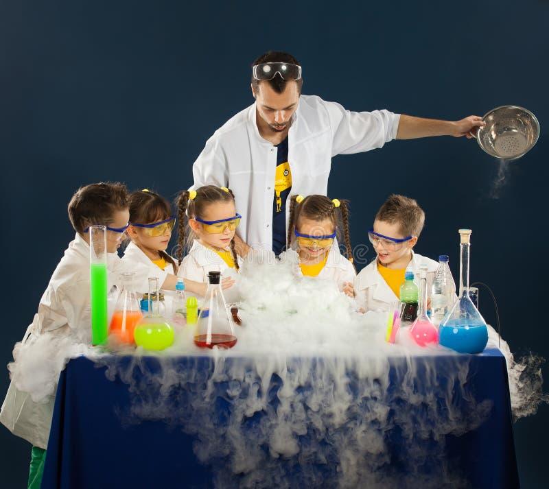 Szczęśliwi dzieciaki z naukowem robi nauce eksperymentują w laboratorium obrazy stock