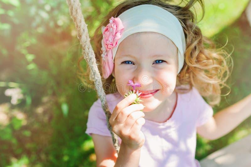 Szczęśliwi dziecko dziewczyny odory kwitną na huśtawce w lecie obraz royalty free
