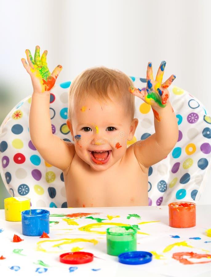 Szczęśliwi dziecko remisy z barwionymi farb rękami obraz stock