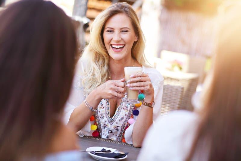 Szczęśliwi dziewczyna przyjaciele w kawiarni podczas lato czasu zdjęcie royalty free
