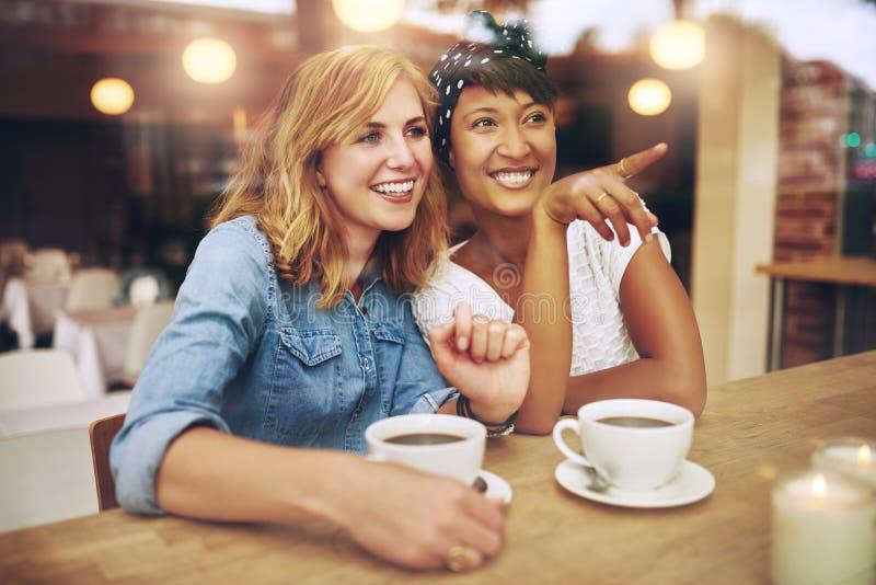 Szczęśliwi dziewczyna przyjaciele wskazuje i ono uśmiecha się zdjęcie royalty free