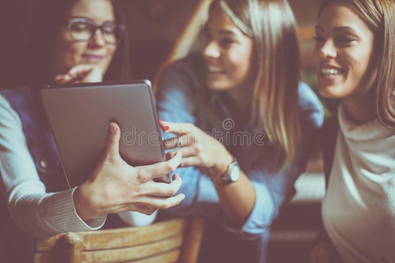 Szczęśliwi dziewczyna ucznie w kawiarni używać cyfrową pastylkę zdjęcia royalty free