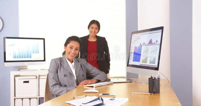 Szczęśliwi etniczni bizneswomany siedzi w biurze obraz royalty free