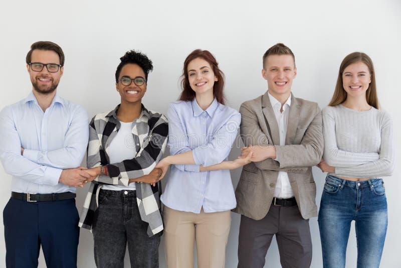 Szczęśliwi etniczni drużynowi ludzie trzyma ręki stoi w rzędzie fotografia stock