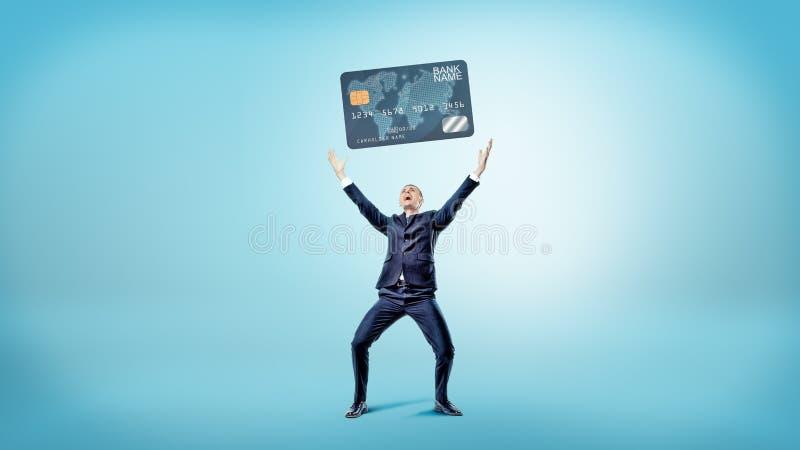 Szczęśliwi i zwycięscy biznesmenów stojaki na błękitnym tle i podtrzymywali gigantyczną rodzajową kredytową kartę fotografia stock
