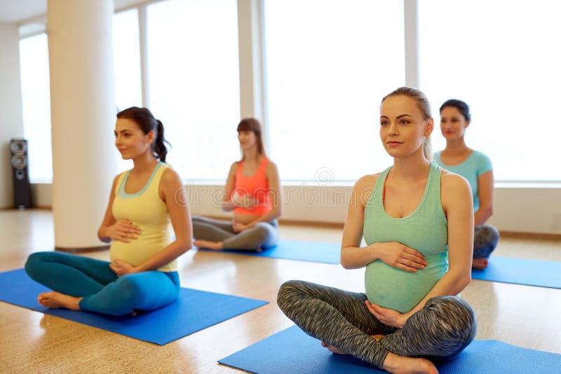 Szczęśliwi kobieta w ciąży ćwiczy przy gym joga zdjęcia royalty free