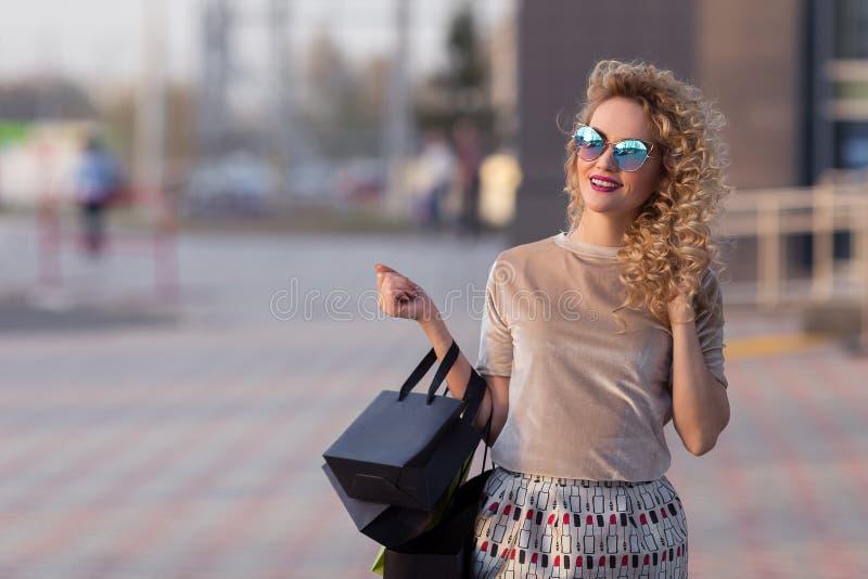 Szczęśliwi kobiety mienia torba na zakupy i ono uśmiecha się zdjęcia royalty free