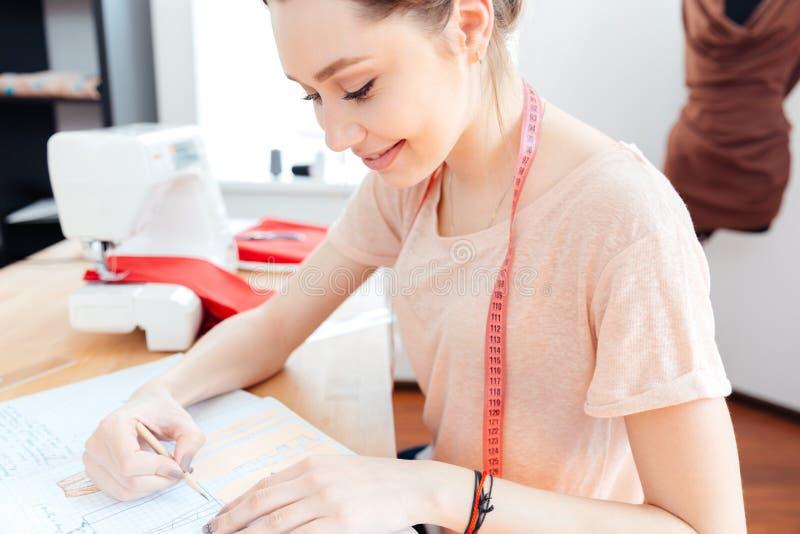 Szczęśliwi kobiety szwaczki rysunku i obsiadania wzory w notatniku fotografia stock