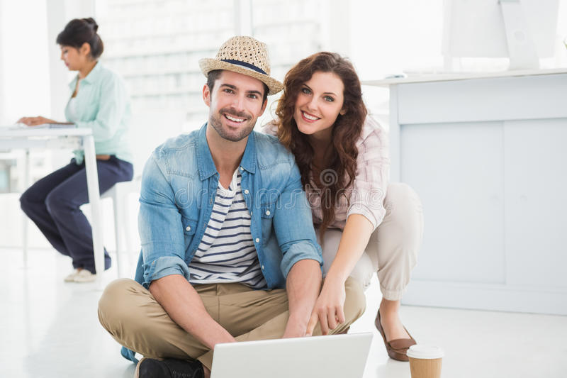 Szczęśliwi koledzy siedzi na podłogowym używa laptopie obraz stock