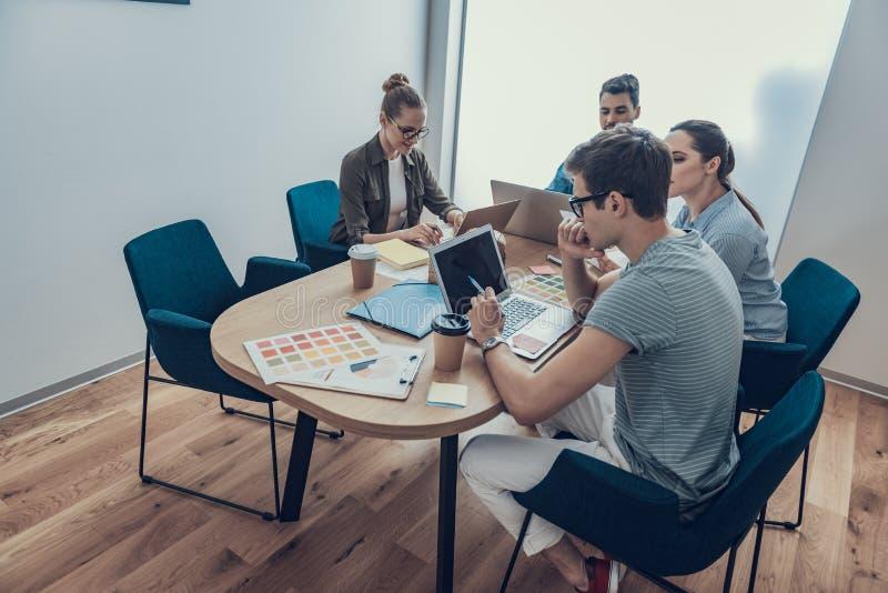 Szczęśliwi koledzy studing nowego projekt z partnerami w workroom obraz royalty free