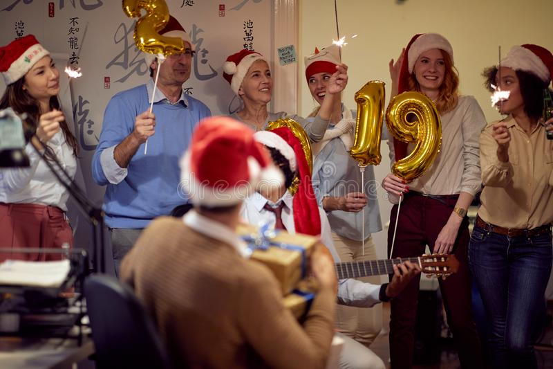 Szczęśliwi koledzy w Santa nakrętkach ma Bożenarodzeniową zabawę obraz royalty free