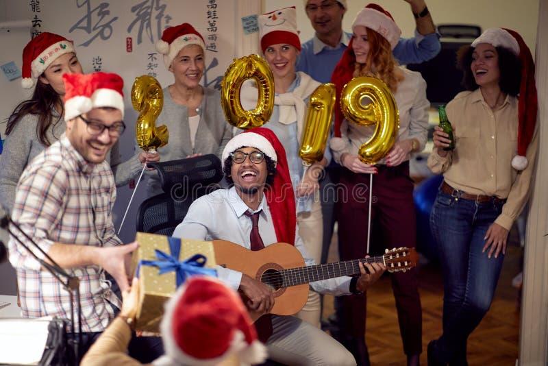 Szczęśliwi koledzy w Santa nakrętkach ma Bożenarodzeniową zabawy i sztuki gitarę obrazy stock