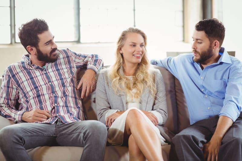 Szczęśliwi ludzie biznesu dyskutuje podczas gdy siedzący na kanapie zdjęcia royalty free