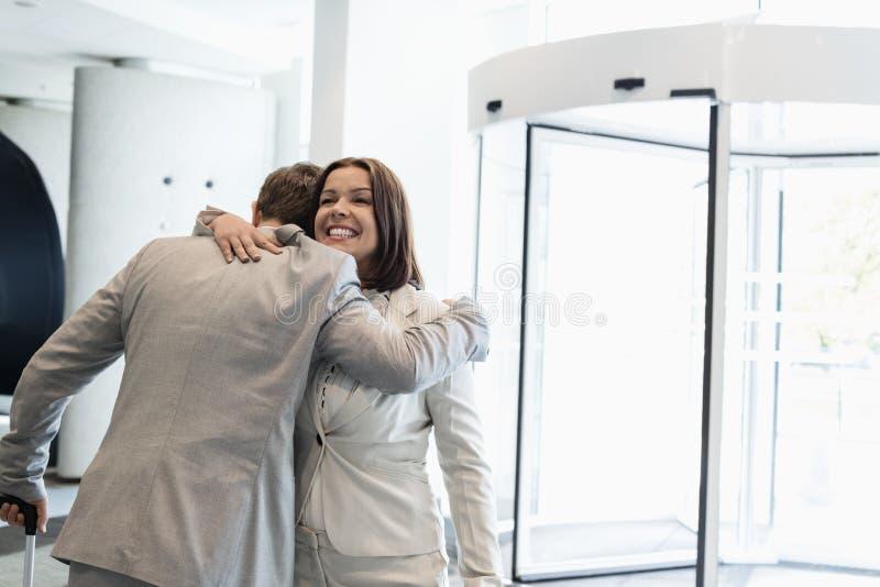 Szczęśliwi ludzie biznesu obejmuje przy jaskrawy zaświecającym convention center obraz stock
