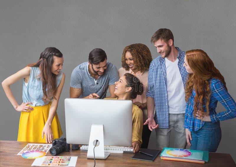 Szczęśliwi ludzie biznesu opowiada przeciw popielatemu tłu przy biurkiem obraz stock