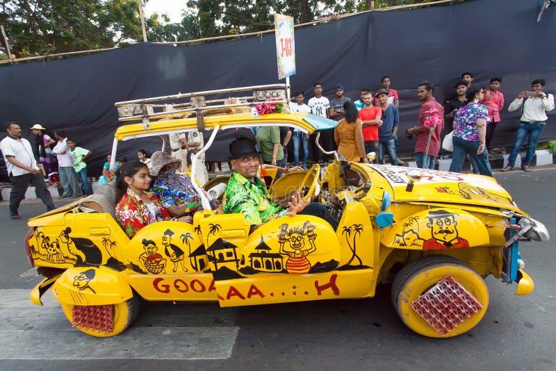 Szczęśliwi ludzie jedzie w żółtym retro samochodzie na zatłoczonej ulicie podczas tradycyjnego Goa karnawału obraz royalty free