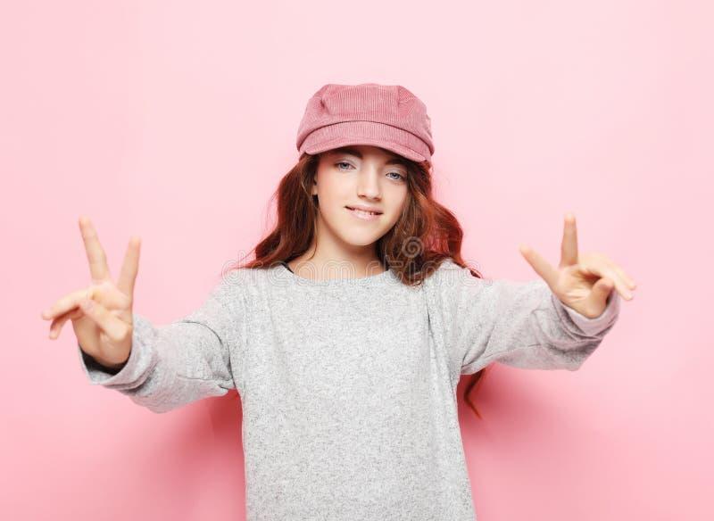 Szczęśliwi ludzie pojęć - uśmiechający się małej kędzierzawej dziewczyny pokazuje pokoju gest z palcami, zamyka up zdjęcia stock