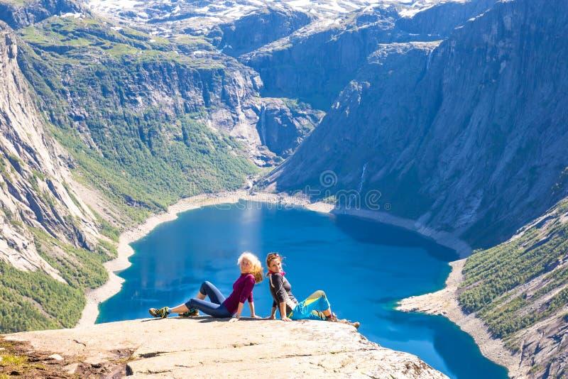 Szczęśliwi ludzie relaksują w falezie podczas wycieczki Norwegia Trolltunga wycieczkuje trasę zdjęcia stock