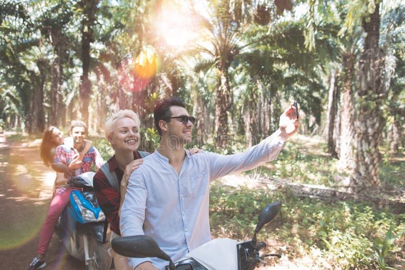 Szczęśliwi ludzie Robi Selfie portretowi Jeździeckiej hulajnoga I Cieszy się wakacje wycieczki samochodowej Dwa pary Biorą jaźni  obrazy royalty free
