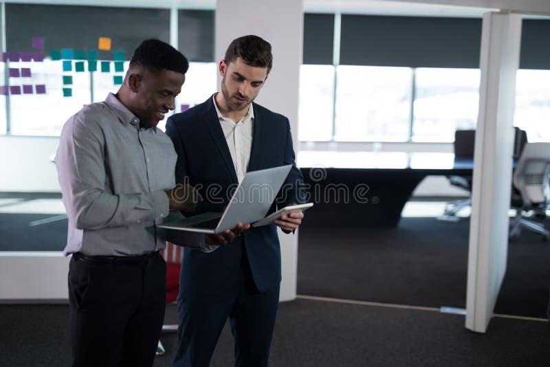 Szczęśliwi męscy kierownictwa używa laptop i cyfrową pastylkę zdjęcia stock