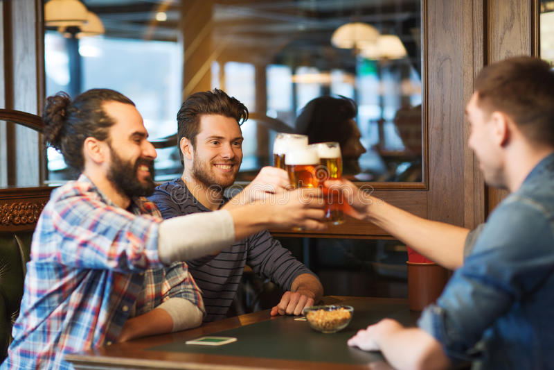 Szczęśliwi męscy przyjaciele pije piwo przy barem lub pubem zdjęcie royalty free