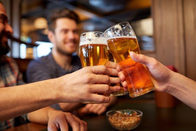 Szczęśliwi męscy przyjaciele pije piwo przy barem lub pubem fotografia stock