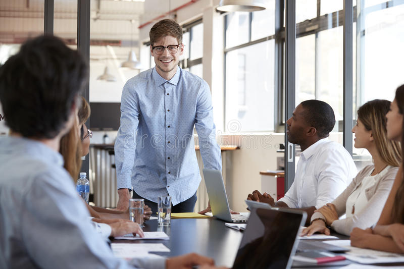 Szczęśliwi młodych człowieków stojaki adresuje drużyny przy biznesowym spotkaniem zdjęcie royalty free