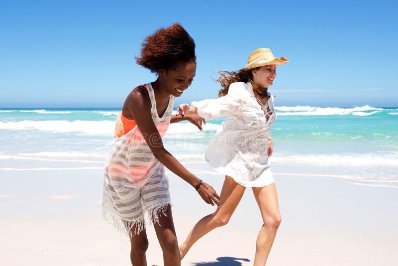 Szczęśliwi młodzi żeńscy przyjaciele biega na plaży zdjęcia stock