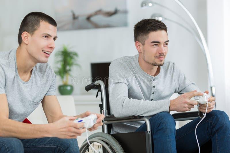 Szczęśliwi młodzi bracia bawić się wideo gry jeden handicaped zdjęcia stock