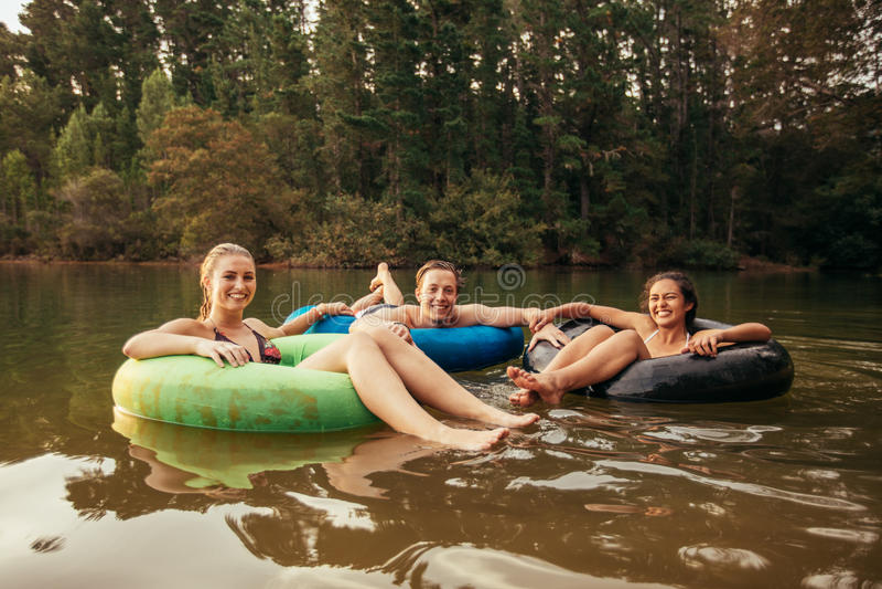 Szczęśliwi młodzi dorosli na wewnętrznych tubkach w jeziorze obraz royalty free