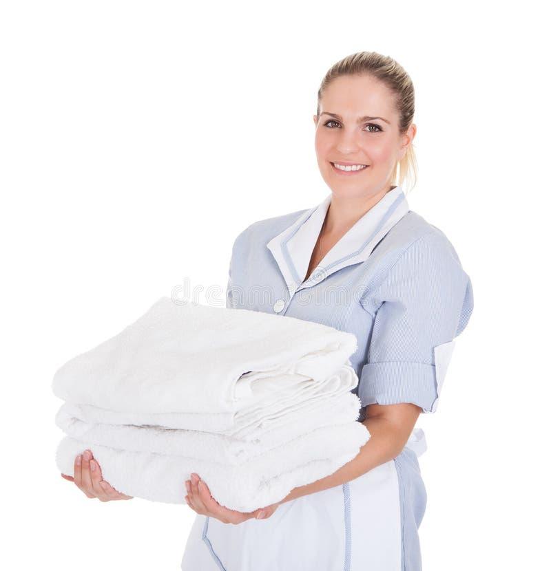 Szczęśliwi młodzi gosposi mienia ręczniki obraz stock