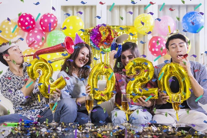 Szczęśliwi młodzi ludzie świętują nowego roku 2020 fotografia stock