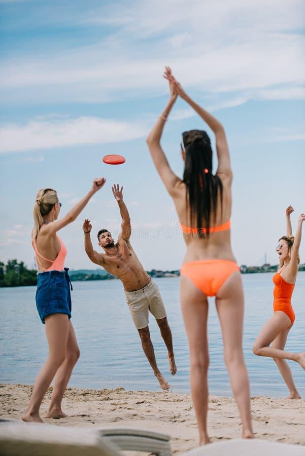 szczęśliwi młodzi ludzie bawić się z latającym dyskiem zdjęcie royalty free