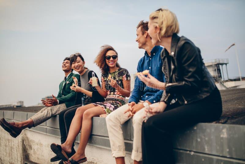Szczęśliwi młodzi ludzie bawi się na dachu zdjęcia stock