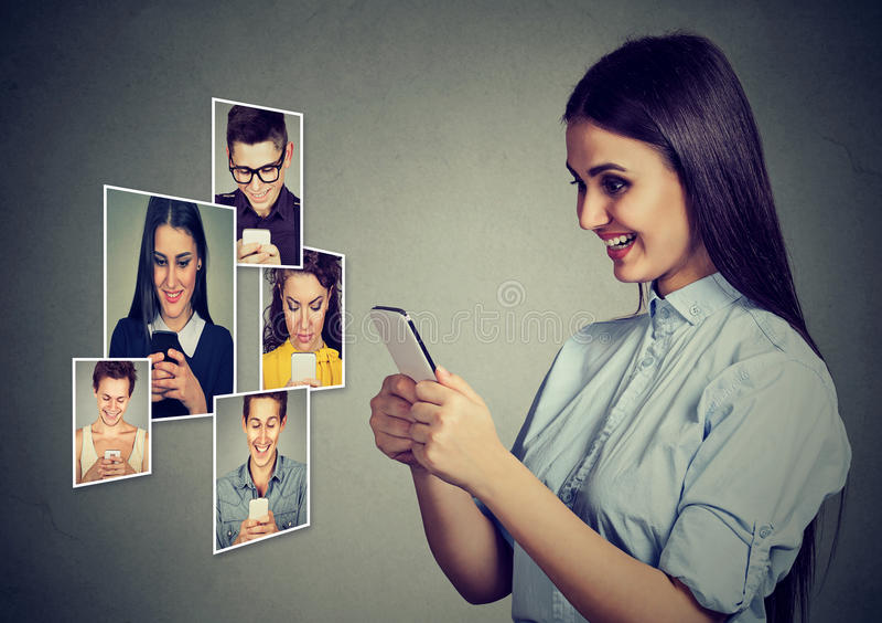 Szczęśliwi młodzi ludzie mężczyzna i kobiety używa mobilny mądrze telefonu ono uśmiecha się zdjęcie stock