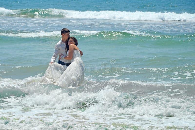 Szczęśliwi młodzi ludzie obejmują i śmiech w nawadnia ocean indyjski Poślubiać i miesiąc miodowy w zwrotnikach na wyspie zdjęcie stock
