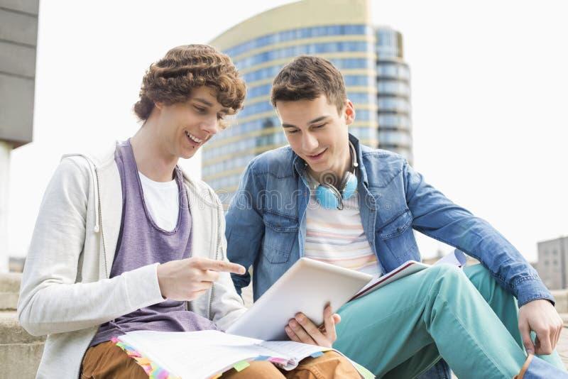 Szczęśliwi młodzi męscy studenci collegu używa cyfrową pastylkę przeciw budynkowi fotografia royalty free