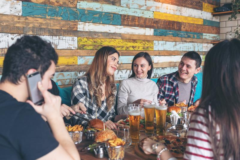 Szczęśliwi młodzi przyjaciele świętuje z pizza hamburgerami i pije piwo przy prętową restauracją zdjęcia stock