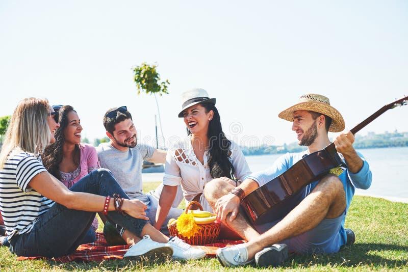 Szczęśliwi młodzi przyjaciele ma pinkin w parku Wszystko są szczęśliwi, mieć zabawę, uśmiechający się gitarę i bawić się, obraz stock