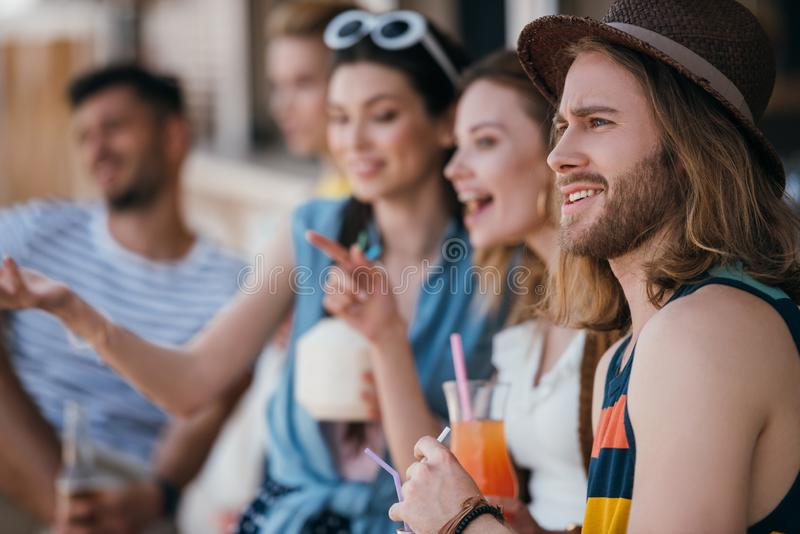 szczęśliwi młodzi przyjaciele pije koktajle i patrzeje daleko od przy plażą zdjęcie royalty free