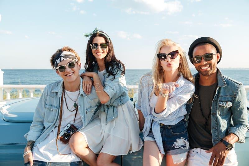 Szczęśliwi młodzi przyjaciele stoi buziaka outdoors i wysyła zdjęcie stock