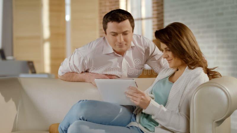 Szczęśliwi młodzi rodzinni dopatrywanie obrazki na pastylce wpólnie, przyjemni wspominki obraz stock