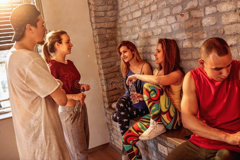 Szczęśliwi młodzi tancerze zaludniają mieć przerwę w studiu przy tanami obrazy stock