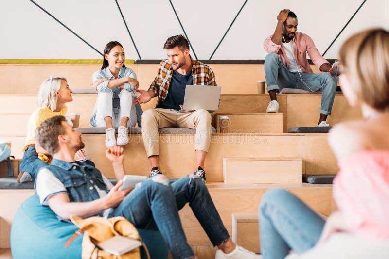 szczęśliwi młodzi ucznie wydaje czas wpólnie przy szkołą wyższą zdjęcia stock