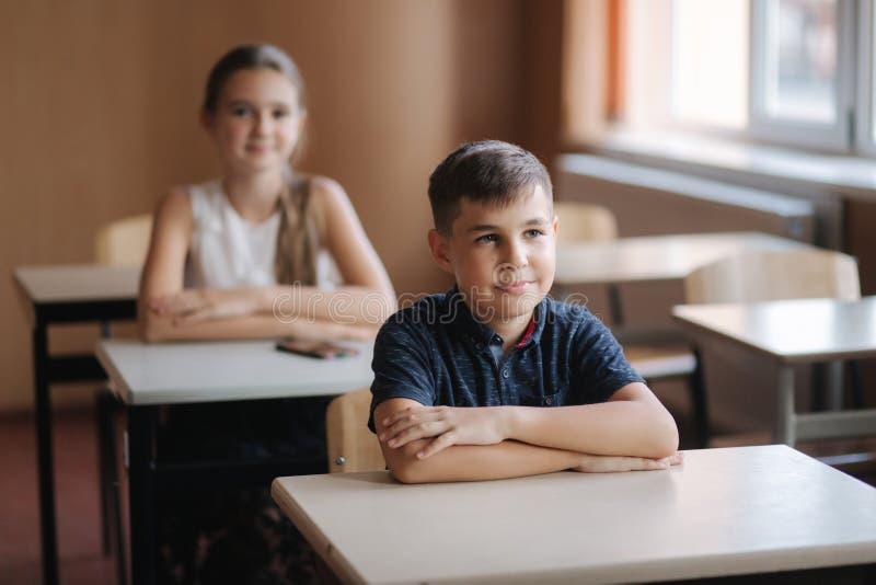 Szczęśliwi małe dzieci w szkole podstawowej Chłopiec i dziewczyn nauka Dziecko podwyżki ręka w górę zdjęcie royalty free