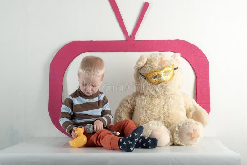 Szczęśliwi małe dzieci z zabawkami bawić się w domu Zabawkarski karton TV Mikrofon, występ obraz royalty free