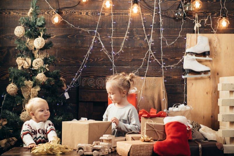 Szczęśliwi mali dzieciaki w Santa kapeluszu z teraźniejszością boże narodzenia Zima evening w domu Otwarcie prezenty na Bożenarod obraz stock
