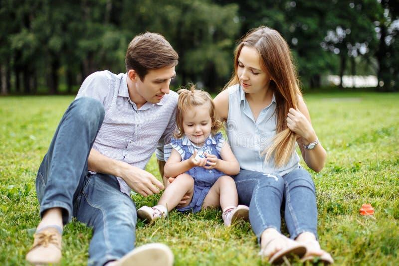 Szczęśliwi matki, ojca i córki dmuchania bąble w parku, zdjęcia stock