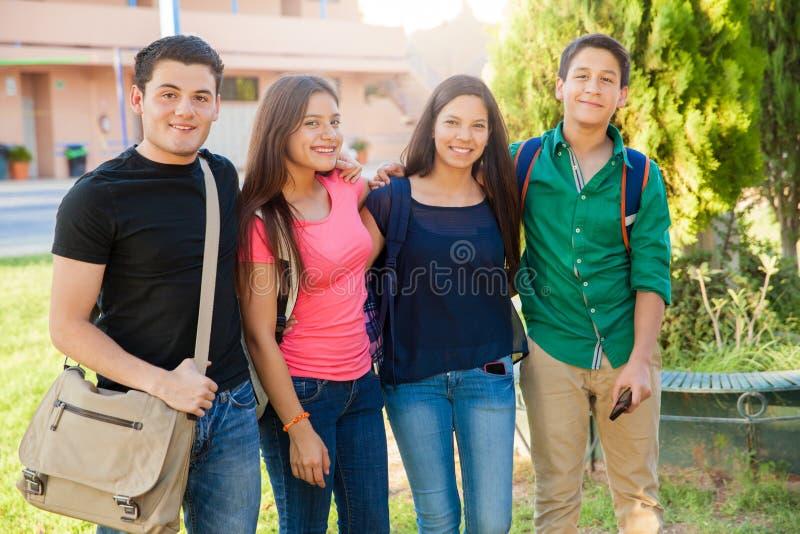 Szczęśliwi nastolatkowie przy szkołą zdjęcia stock